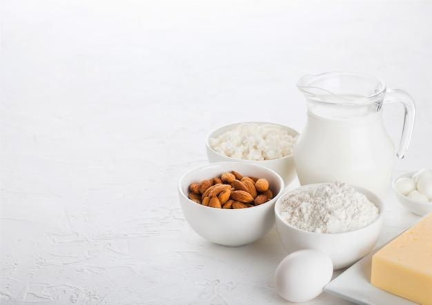 Świezi nabiały na bielu stole. szklany słoik mleka, miska twarogu i mąki do pieczenia i orzechów migdałów. jajka i ser