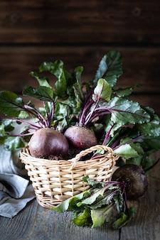 Świezi organicznie czerwoni buraki z liśćmi w łozinowym koszu na drewnianym stole. naturalne organiczne warzywa. jesienne zbiory. rustykalny. kopia przestrzeń