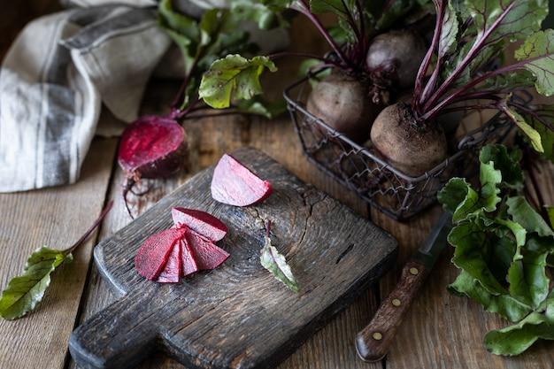 Świezi organicznie czerwoni buraki z liśćmi w łozinowym koszu na drewnianym stole. naturalne organiczne warzywa. jesienne zbiory. rustykalny