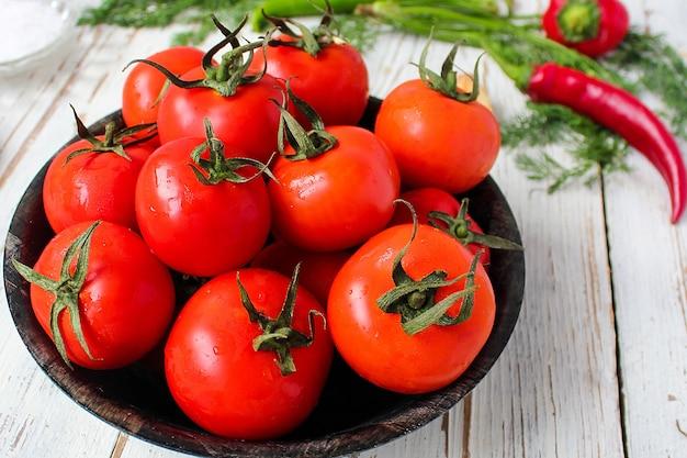 Świezi organicznie czerwoni pomidory w czarnym talerzu na białym drewnianym stole.