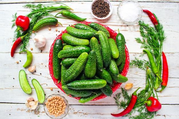 Świezi organicznie ogórki w czerwonym koszu na białym drewnianym stole z zielenią, czerwień i czosnek