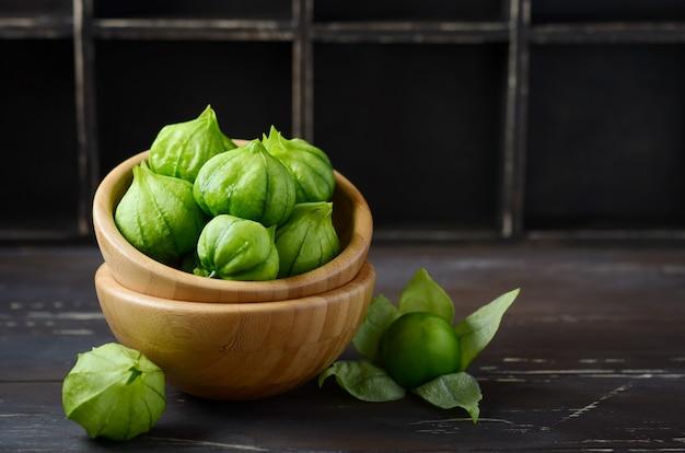 Świezi organicznie zieleni tomatillos z plewą na nieociosanym drewnianym stole (pęcherzyca philadelphica).