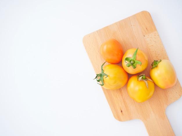 Świezi pomidory na drewnianej tnącej desce.