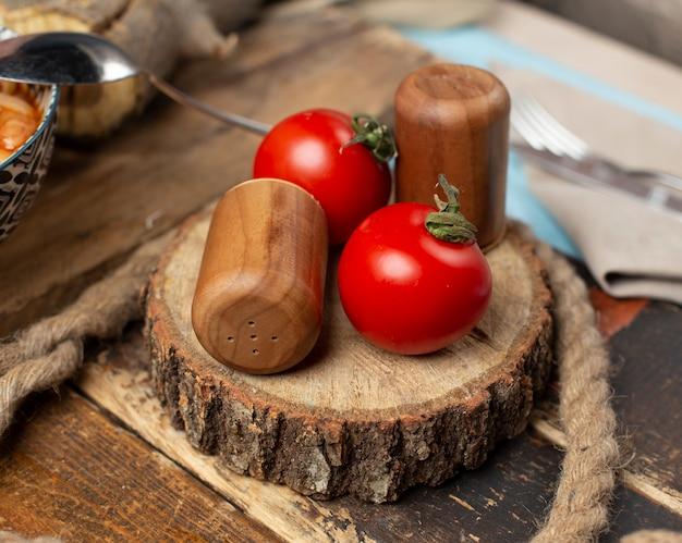 Świezi pomidory na kawałku drewno.