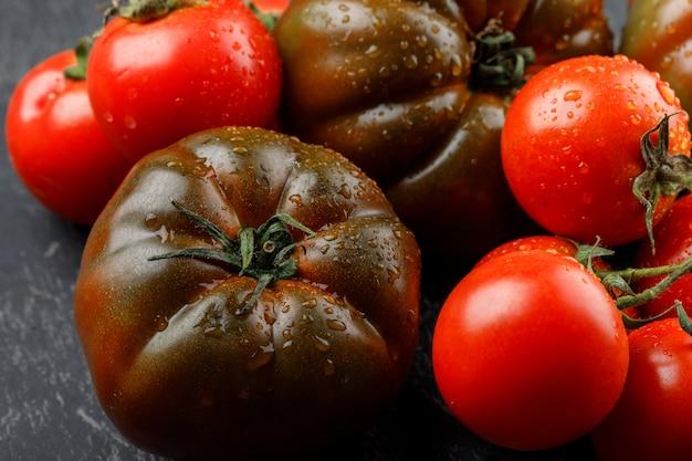 Świezi pomidory na szarej ścianie. zbliżenie.