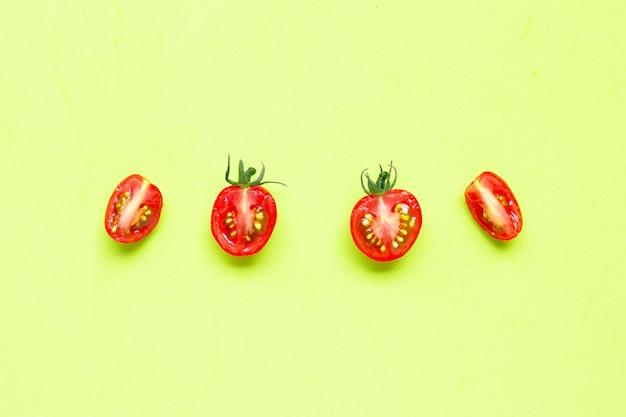 Świezi pomidory, połówki cięcie odizolowywający na zielonym tle.