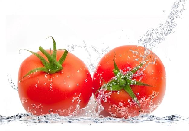 Świezi pomidory spada w wodzie