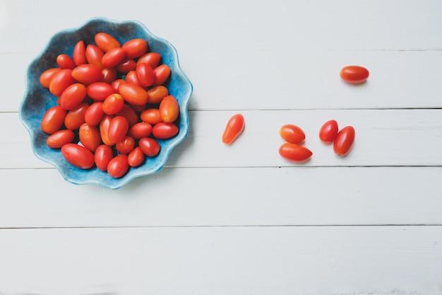 Świezi pomidory w błękitnym pucharze na białym tle. widok z góry.