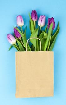 Świezi purpurowi tulipanowi kwiaty w brown papierze nad błękit powierzchnią