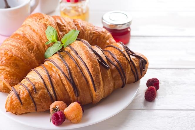 Świezi smakowici croissants z jagodami na białym drewnianym tle