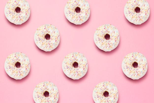 Świezi smakowici słodcy pączki na różowym tle. koncepcja fast food, piekarnia, śniadanie, słodycze. minimalizm. wzór. leżał płasko, widok z góry.