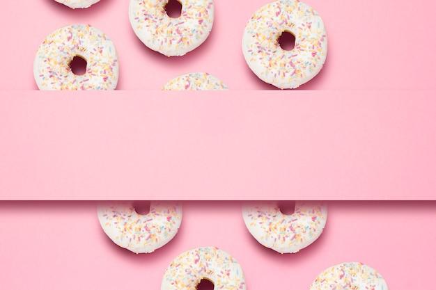 Świezi smakowici słodcy pączki na różowym tle. miejsce na tekst. koncepcja fast food, piekarnia, śniadanie, słodycze. minimalizm. wzór. leżał płasko, widok z góry, miejsce.