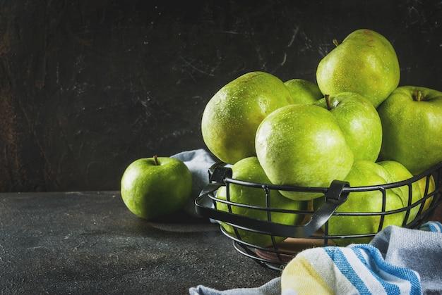 Świezi surowi organicznie gospodarstwo rolne zieleni jabłka w czarnym metalu koszu, ciemny ośniedziały, copyspace