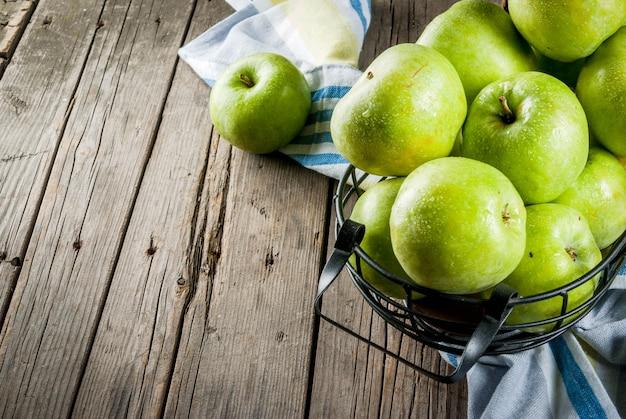 Świezi surowi organicznie gospodarstwo rolne zieleni jabłka w czarnym metalu koszu, stary nieociosany drewniany, copyspace