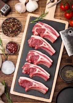 Świezi surowi rzeźnicy jagnięciny kotlety wołowe na desce do krojenia z rocznika siekierą mięsa i młot na drewniane