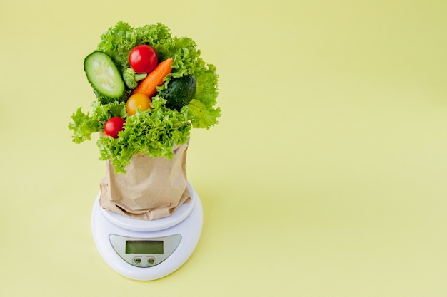 Świezi warzywa dalej ważą na żółtym tle. wegańska i zdrowa koncepcja.