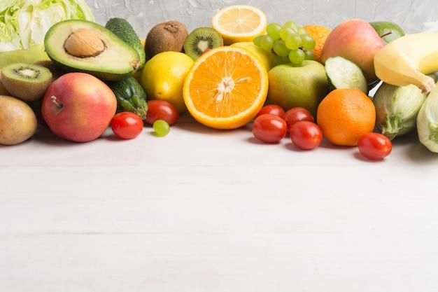 Świezi warzywa i owoc nad białym drewnianym tłem
