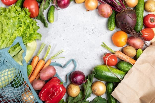 Świezi warzywa w netto torbie i papierowej torbie i kłaść out na betonowym tle z kopii przestrzenią.