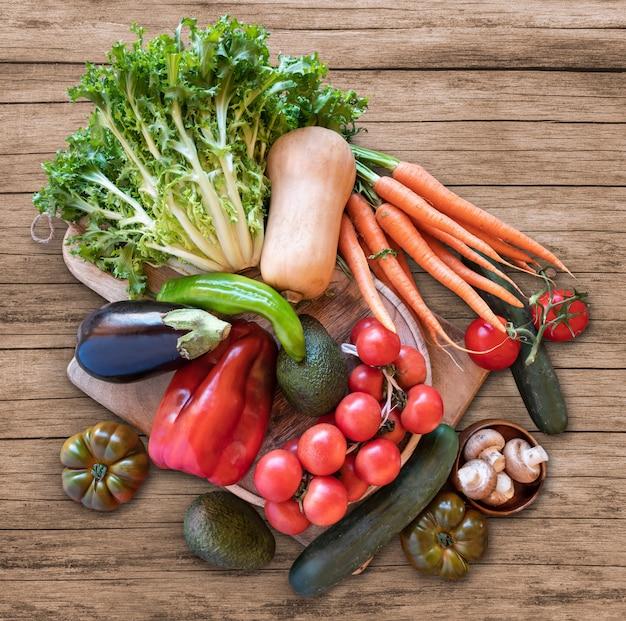 Świezi warzywa właśnie podnoszący od sadu na drewnianym tle, zasięrzutny widok