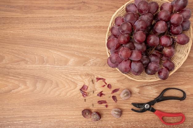 Świezi winogrona na koszykowym drewnianym tle. skopiuj miejsce na dodanie tekstu.