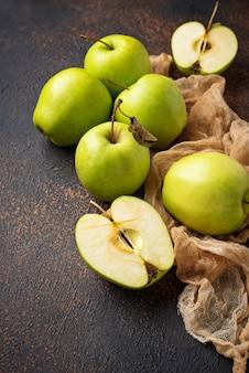 Świezi zieleni jabłka na ośniedziałym tle