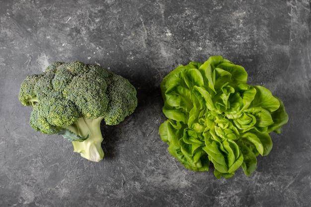 Świezi zieleni warzywa na ciemnym stole, odgórny widok z kopii przestrzenią.