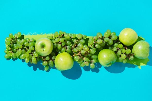 Świezi zieleni winogrona i jabłko na błękitnym tle z szumem farby