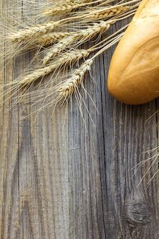 Świeżo bagietki pieczone kolce chleba i pszenicy na drewnianym stole.