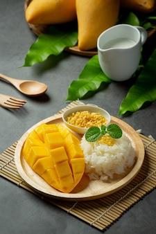Świeżo dojrzałe mango i lepki ryż z mlekiem kokosowym na ciemnej powierzchni