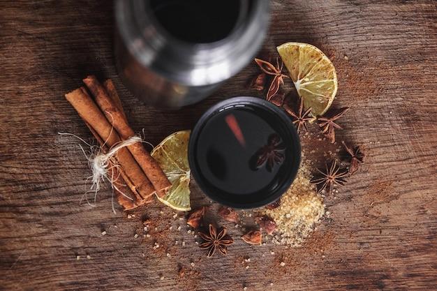 Świeżo domowej roboty grzane wino w misce z pachnącymi gatunkami, owocami cytrusowymi, cytryną na drewnianej desce rusric. leżał płasko. miejsce na tekst.