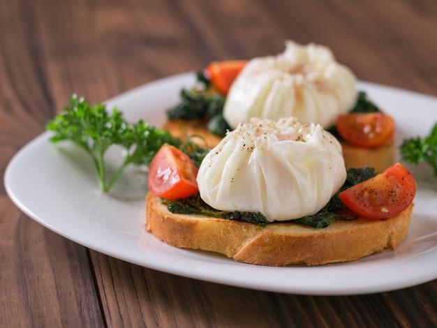 Świeżo gotowane jajka na kromkach chleba na białym talerzu. wegetariańska przekąska z jajkiem w koszulce.