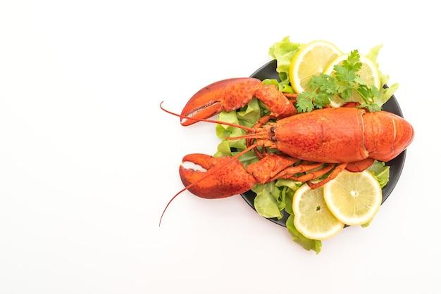 Świeżo gotowanego homara z warzywami i cytryną na białym tle na białej powierzchni