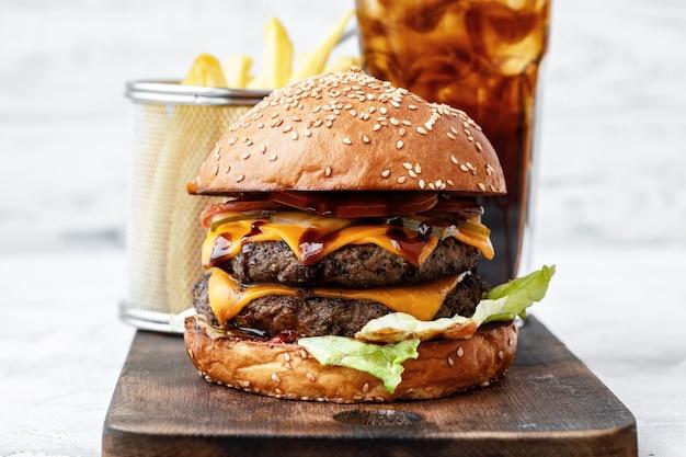 Świeżo gotowany burger na desce na jasnym tle, widok z przodu