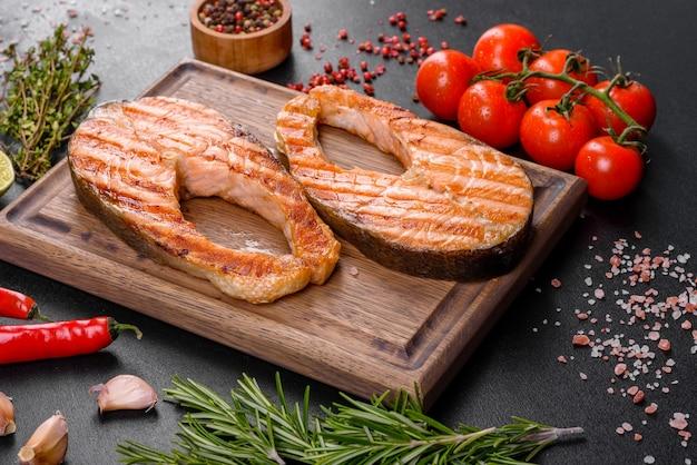 Świeżo gotowany pyszny stek z łososia z przyprawami i ziołami pieczony na grillu. zdrowe owoce morza