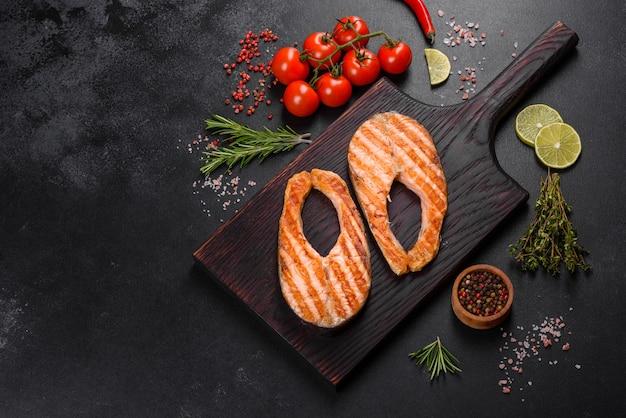 Świeżo gotowany pyszny stek z łososia z przyprawami i ziołami pieczony na grillu