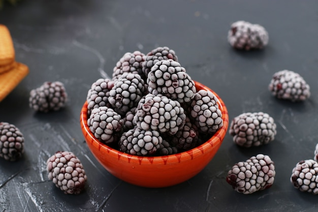 Świeżo mrożone jeżyny w misce na ciemnym tle, mrożone jagody na zimę, układ poziomy