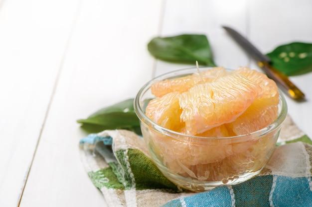 Świeżo obrane pomelo lub grejpfrut w szklanej misce na białym drewnie