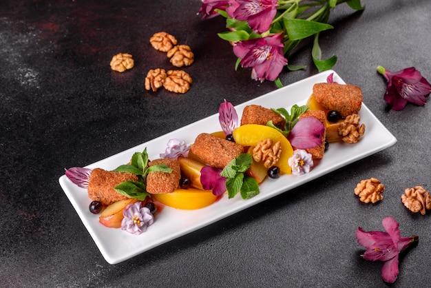 Świeżo pachnące paluszki serowe z pieczonym jabłkiem i brzoskwinią ozdobione kwiatami na białym talerzu