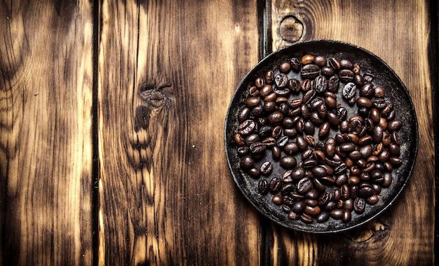 Świeżo palona kawa na patelni na drewnianym stole.