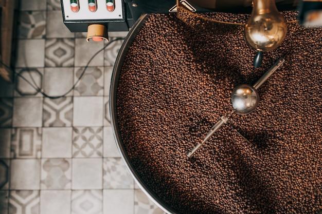 Świeżo palone aromatyczne ziarna kawy na nowoczesnej palarni kawy.