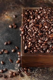 Świeżo palone ziarna kawy w drewnianym pudełku