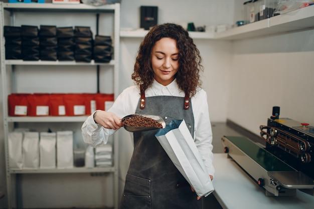 Świeżo palonych ziaren kawy młoda kobieta robotnik maszyna do pakowania w próżniowo zamkniętej torbie.