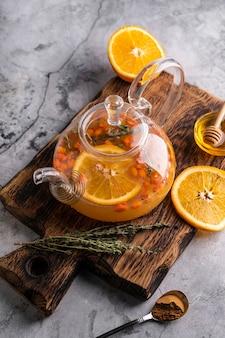 Świeżo parzona herbata z rokitnika w przezroczystym czajniczku z owocami
