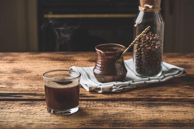 Świeżo parzona kawa po turecku w szklance. cezve i słoik palonych ziaren kawy.