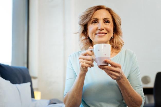 Świeżo parzona kawa. uśmiechnięta, krótkowłosa dojrzała dama, zadowolona ze swojego spokojnego poranka podczas picia kawy i budowania planów