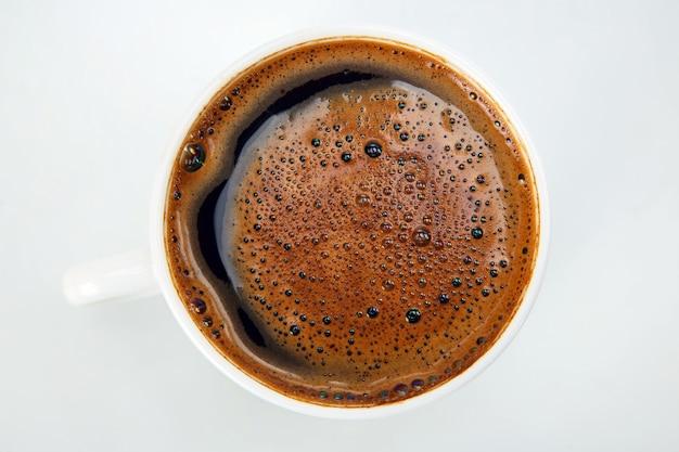 Świeżo parzona kawa w filiżance na białym tle zbliżenie