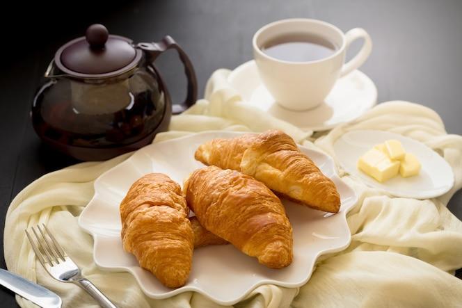 Świeżo piec croissants i filiżanka herbata na białym talerzu na ciemnym stołowym tle.