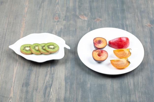 Świeżo pokrojone śliwki z soczystym kiwi na drewnianym stole