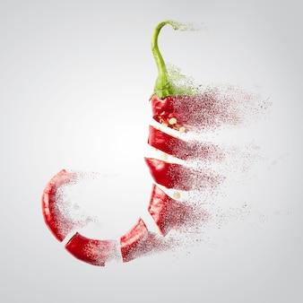 Świeżo posiekane czerwone papryczki chili w proszku chili lecą na białej powierzchni