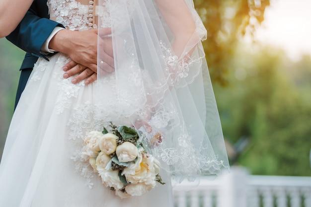 Świeżo poślubiona para. dzień ślubu. bukiet panny młodej w rękach, uścisk pana młodego.